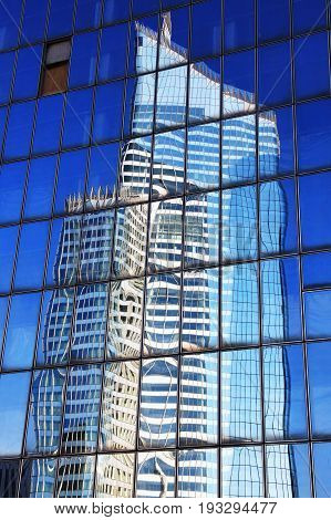 Reflection of a skyscraper in glass office windows