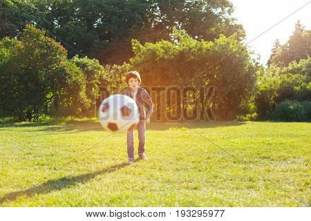 Active leisure. Emotional energetic talented child enjoying the game while having an active leisure and spending it in the park