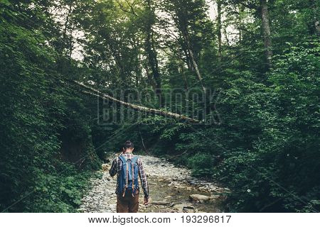 Hiker Man Walks Along Mouth Of Mountain River In Deep Forest Rear View. Trek Hiking Destination Experience Lifestyle Concept