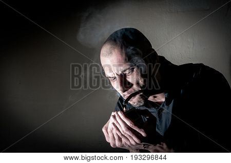 Addict. Man smoking. Cigarette addict. Dark image. Smoking cigarette.