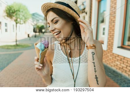 Happy young woman in straw hat and white dress eating ice cream outdoor
