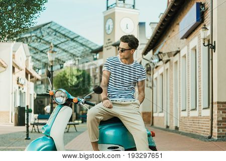 Man Sitting On Retro Scooter Parked On Street And Looking Away