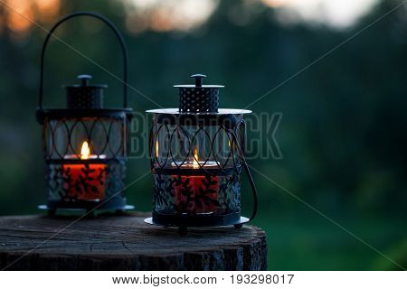 Burning candles inside old lanterns on old wooden stump in the background of sunset