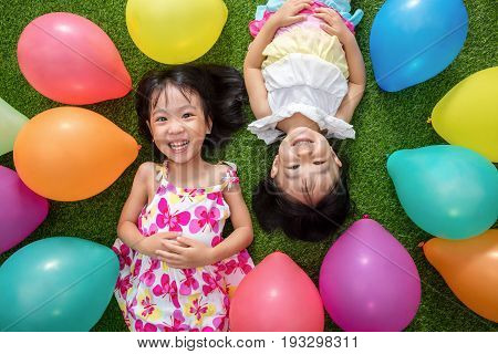 Asian Little Chinese Girls Lying On Grass Amongst Colorful Balloons