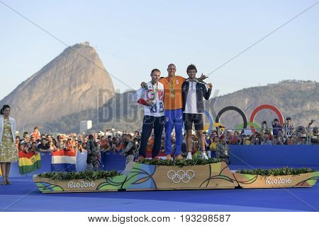 Rio de Janeiro Brazil - august 14 2016: Dorian van RIJSSELBERGHE (NED) gold medal Nick DEMPSEY (GBR) silver and Pierre le COQ (FRA) bronze during Podium ceremony Men's rs-x sailing of the Rio 2016 Olympics Games
