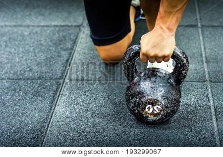 Kettle bell workout. Woman holding kettle bell with her hand on the gym floor. Selective focus and light.