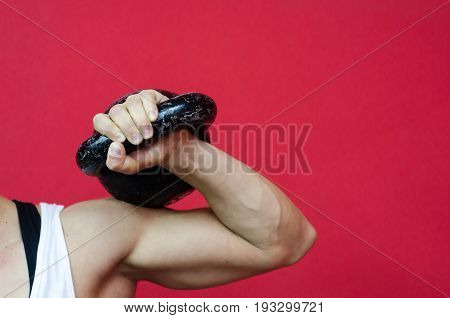 Kettle bell workout. Woman holding kettle bell with her hand. Selective focus.