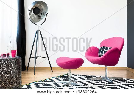 Pink swan armchair and matching stool on a patterned black and white carpet.