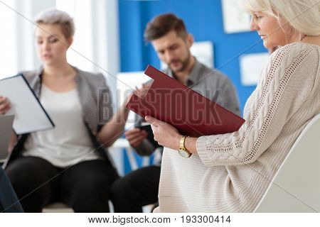 Elderly manager looking at the red questionnaire