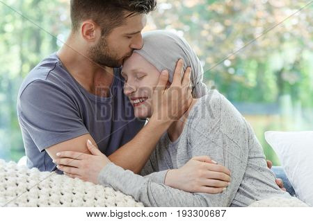 Young sick woman being kissed on the head