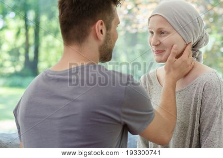 Loving husband touching his sick wife's smiling face