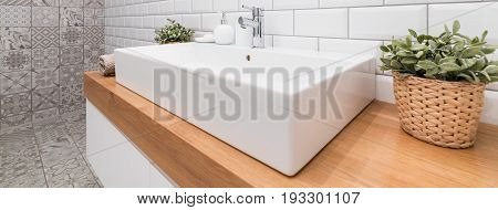 Close-up of big porcelain sink in new modern bathroom. On a wooden wheat plants and folded towel