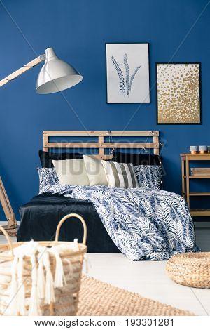 Dark blue bedroom with natural wooden furniture