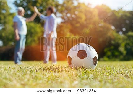 Sport challenge. Emotional original easy going gentleman giving his dad a high five while inviting him for a game in the park and being glad seeing him