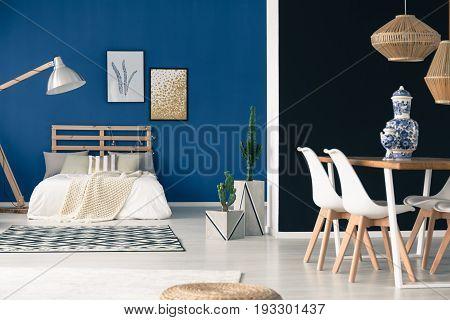 Inspiring blue studio with stylish wooden furniture