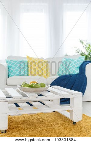 White elegant couch and DIY pallet end table in bright living room