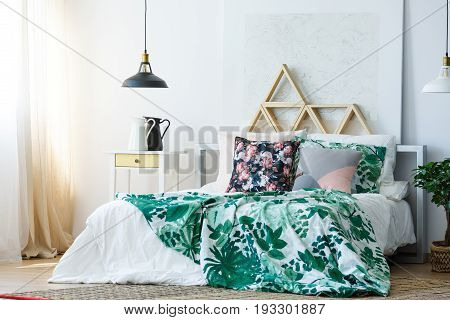 Green and white floral bedclothes in stylish bedroom