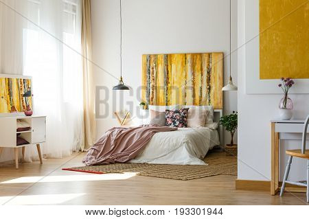 Spacious warm bedroom with contemporary artworks on the walls