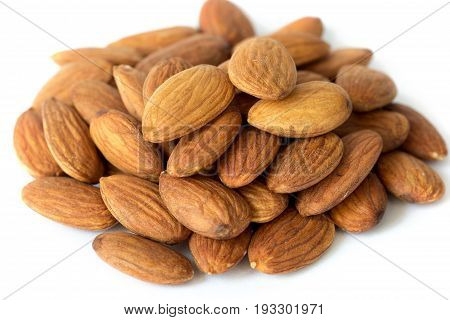 Heap of brown apricot kernels on white background close up