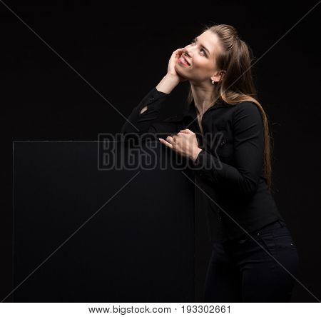 Young wistful woman portrait of a confident businesswoman showing presentation, pointing placard black background. Ideal for banners, registration forms, presentation, landings, presenting concept..