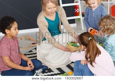 Young kindergarten teacher playing games with children