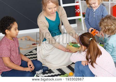 Young kindergarten teacher playing games with children