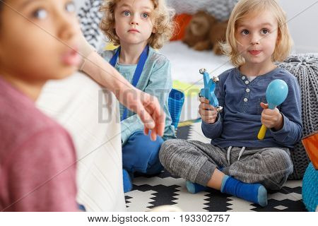 Cute little girl playing rattles sitting on a carpet in kindergarten