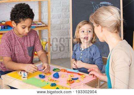 Boy and girl having fun with kindergarten teacher during classes