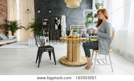 Young attractive woman with red hair drinking tea in fancy industrial apartment