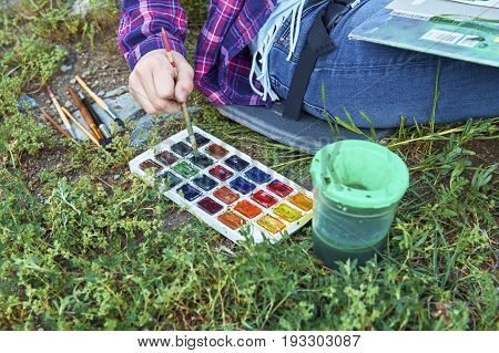 Close-up of a teen girl's hand dunking a paintbrush into the set of watercolor paints