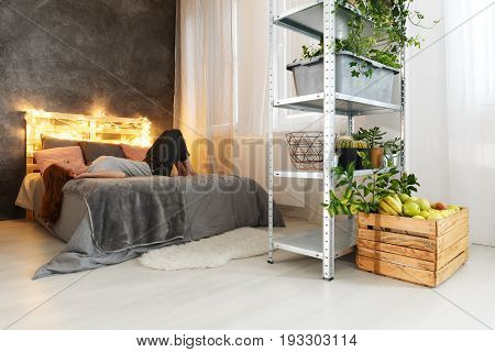 Young attractive woman relaxing on stylish DIY bed in industrial apartment