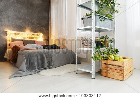 Young woman with red hair lying on cozy bed in stylish modern apartment