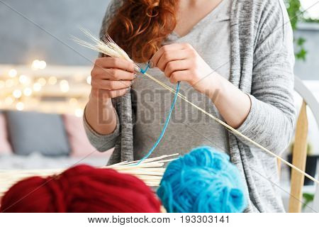 Young woman making colorful creative yarn decorations