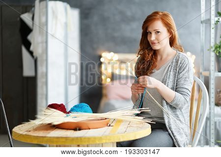 Smiling young woman making creative decorations at stylish modern home