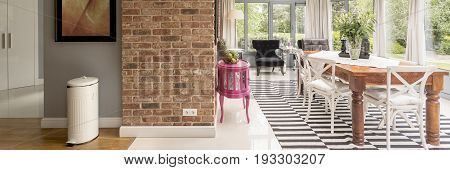 Stylish scandinavian dining area with wooden table chairs patterned flooring in orangery