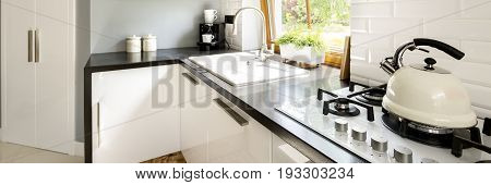 Clear and simple kitchen with gas burners on which stands the traditional kettle