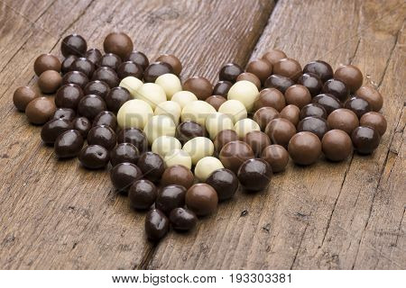 heap of assorted chocolate pralines on wooden table