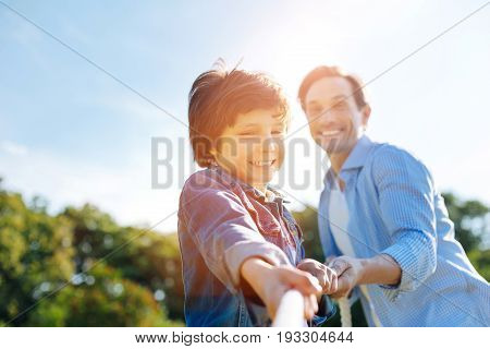 Hold together. Devoted healthy active kid having an active weekend and spending it outdoors while playing sport games with his dad