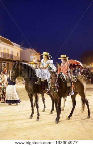 El Rocio Spain - June 1 2017: Female pilgrims on horseback in traditional spanish dress in El Rocio during the Romeria 2017. Province of Huelva Almonte Andalusia Spain