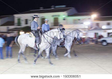 El Rocio Spain - June 1 2017: Pilgrims on horseback in traditional spanish dress in El Rocio during the Romeria 2017. Province of Huelva Almonte Andalusia Spain