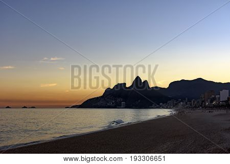 Summer sunset at Ipanema beach in Rio de Janeiro with Two Brothers hill and Gavea stone in background