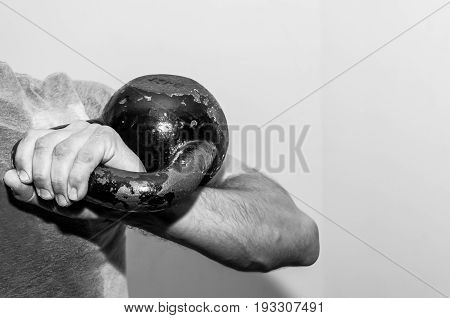 Kettle bell. Man holding old and rusty kettle bell on his shoulder. Black and white. Dark image.