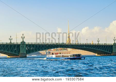 ST PETERSBURG RUSSIA-OCTOBER 3 2016. Palace Bridge and touristic pleasure boat at Neva River and Peter and Paul fortress belfry on the background in St Petersburg. St Petersburg Russia landmarks