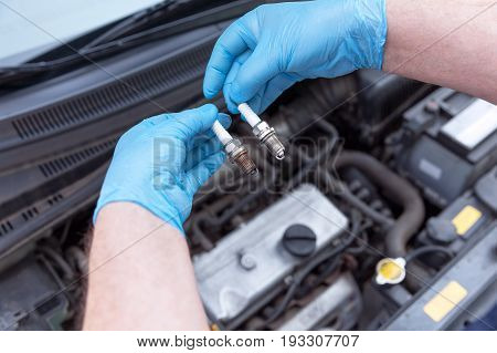 Auto mechanic wearing protective work gloves holds old and new spark plugs over a car engine