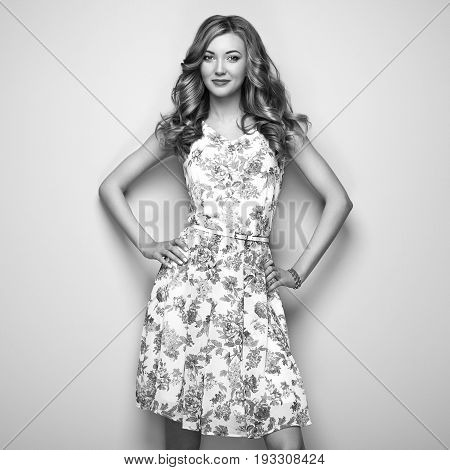Blonde young woman in floral spring summer dress. Summer floral outfit. Stylish wavy hairstyle. Fashion photo. Blonde lady. Black and White photo