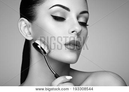 Makeup artist applies skintone with brush. Beautiful woman face. Perfect makeup. Skincare foundation. Makeup artist. Black and White photo