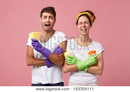 Grieved Couple In White T-shirts And Gloves Holding Sponges And Washing Spray Being Upset Not Wantin