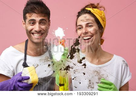Happy Couple With Dirty Faces Tidying Up Window Surface Using Cleanser And Sponges Smiling With Broa