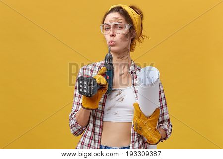 Self-confident Female Builder Wearing Goggles, White Top And Checkered Shirt, Protective Gloves Hold