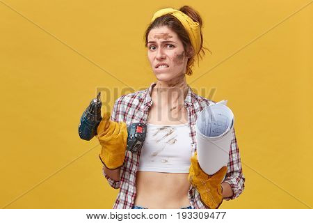Displeased Female Technician Having Dirty Face And Clothes Biting Her Lip And Frowning Face Holding